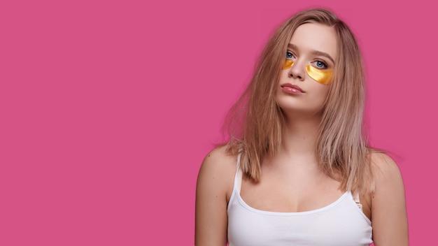 Femme avec des taches sous les yeux sur fond rose isoler. fille fatiguée avec la gueule de bois