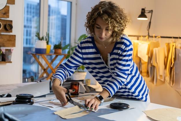 Femme tailleur coupe des échantillons de vêtements de papier brouillon dans l'atelier du studio de conception d'usine de vêtement