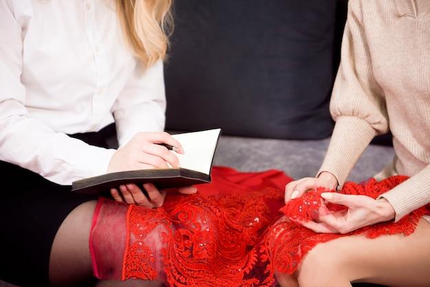 Une femme tailleur note dans un cahier les souhaits du client pour un nouveau costume. personnalisation individuelle.