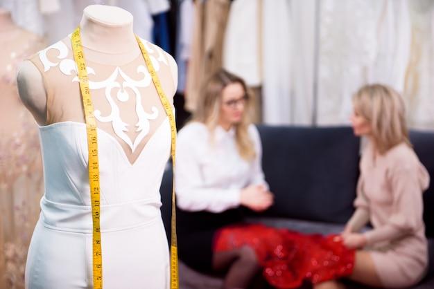 Une femme tailleur parle d'une nouvelle robe avec un client.