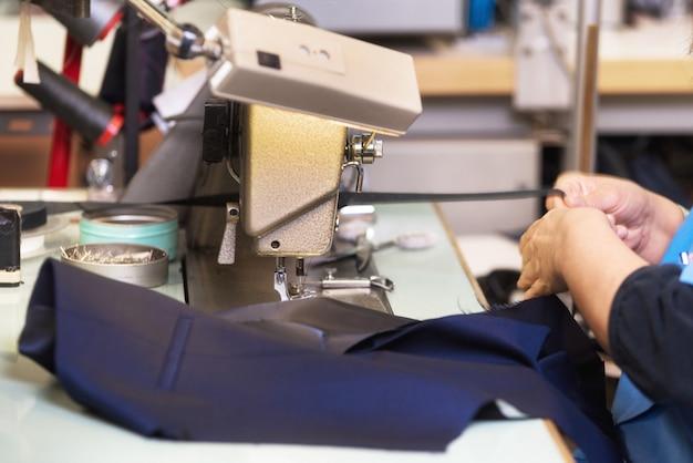 Femme tailleur travaillant sur une machine à coudre. mains. fermer. adaptation. détails.
