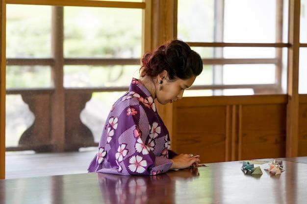Femme talentueuse faisant de l'origami avec du papier japonais