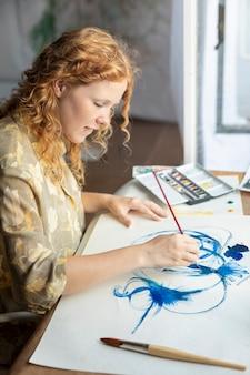 Femme talentueuse grand angle en train de peindre