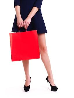 Femme en talons hauts avec sac à provisions rouge debout - isolé sur blanc.