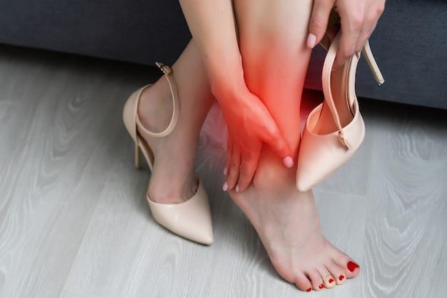 Femme en talons massant les jambes fatiguées.