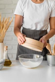 Femme tamisant la farine sur un bol