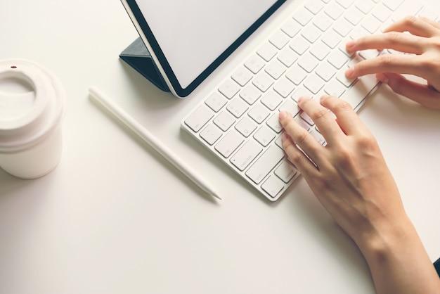 Femme tapant clavier écran d'ordinateur portable et tablette vierge sur la table simulée pour promouvoir vos produits.