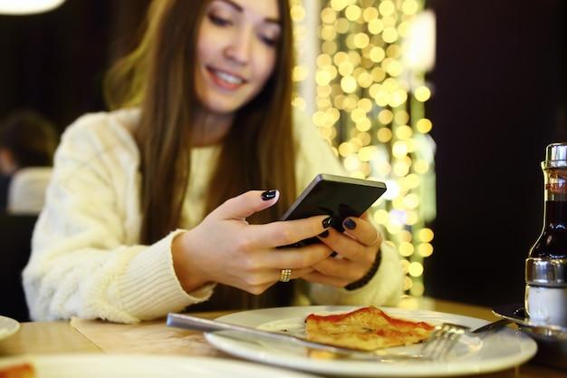 Femme en tapant écrire un message sur le téléphone intelligent dans un café moderne. image recadrée de jolie jeune fille assise à une table avec pizza à l'aide de téléphone portable