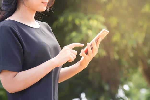 Femme en tapant le message texte sur le téléphone intelligent. jeune femme à l'extérieur sur le téléphone portable.