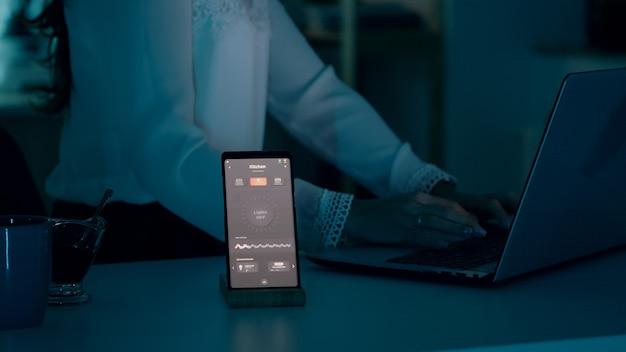 Femme tapant sur un ordinateur portable assis dans la maison avec un système d'éclairage automatisé utilisant la commande vocale sur sma...