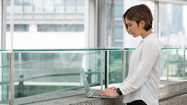 Femme tapant sur un ordinateur portable coup moyen