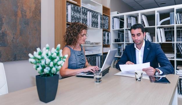 Femme tapant sur un ordinateur portable tandis qu'un homme d'affaires détenant des documents assis à table au bureau