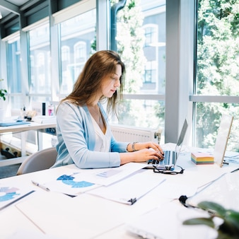 Femme tapant portable dans le bureau