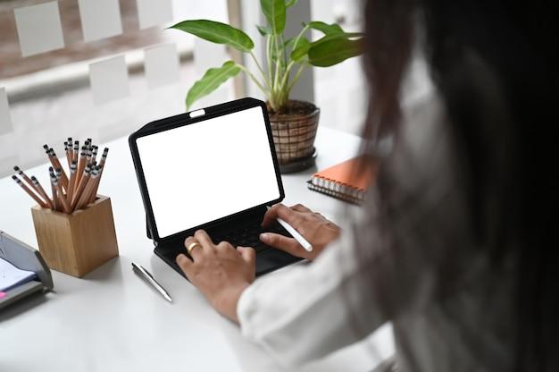 Femme en tapant sur une tablette informatique à écran blanc blanc au bureau