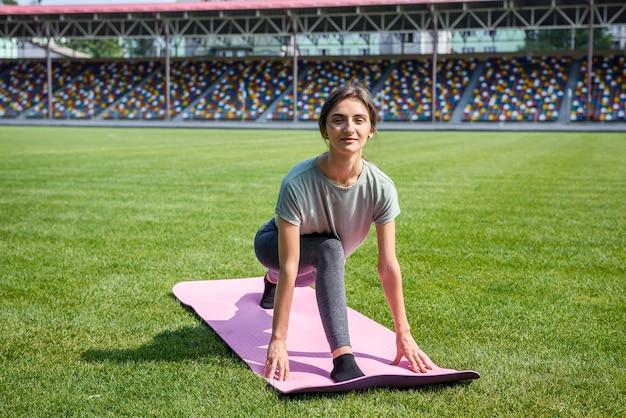 Femme sur tapis de formation à l'extérieur sur l'herbe verte