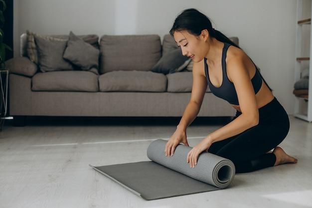 Femme avec tapis de yoga à la maison