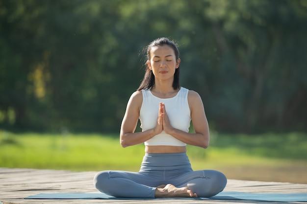 Femme sur un tapis de yoga pour se détendre dans le parc au lac de montagne. femme calme aux yeux fermés pratiquant le yoga, assise à padmasana pose sur tapis, exercice de lotus, jolie fille sportive en tenue de sport.