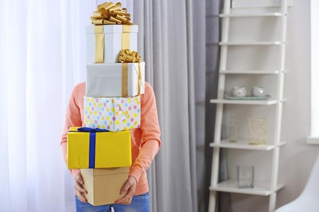 Femme avec tas de cadeaux à la maison