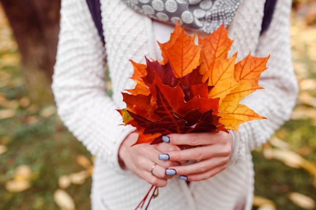 Femme avec un tas de feuilles d'orange