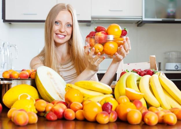 Femme avec des tas de fruits variés