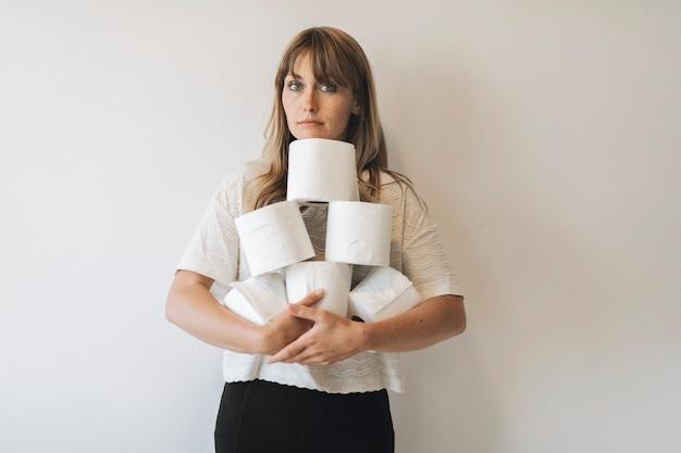 Femme avec un tas de rouleaux de papier toilette