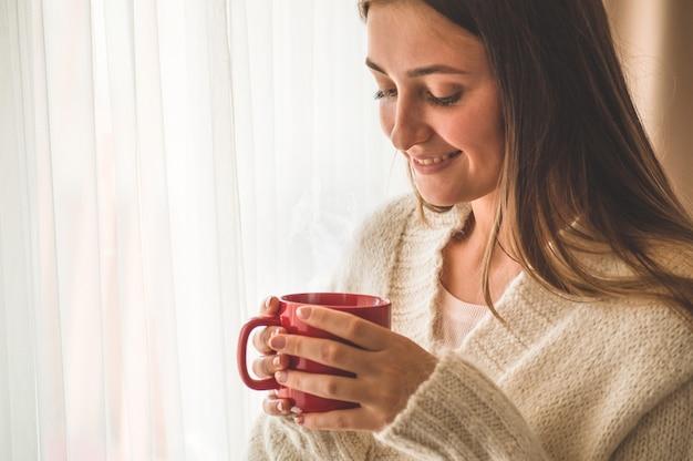 Femme avec tasse de boisson chaude près de la fenêtre. bonjour avec du thé. automne hiver