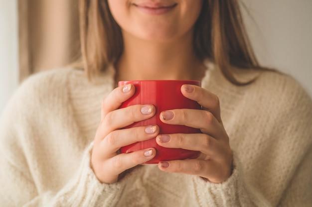 Femme avec tasse de boisson chaude près de la fenêtre