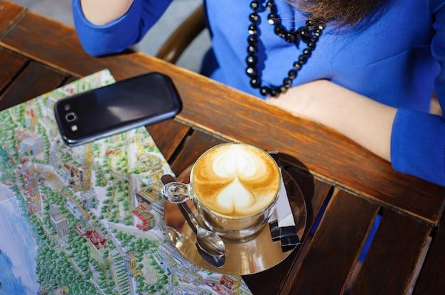 Femme avec une tasse de café, téléphone intelligent et carte