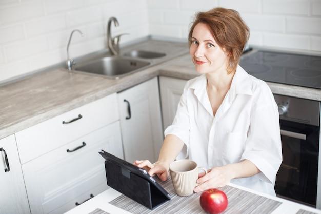 Femme avec une tasse de café ou de thé utilisant un ordinateur portable dans la cuisine à la maison