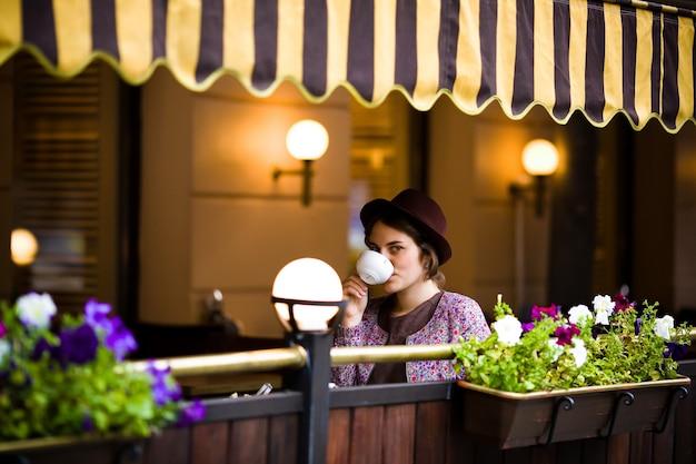 Femme avec une tasse de thé assis dans un café.