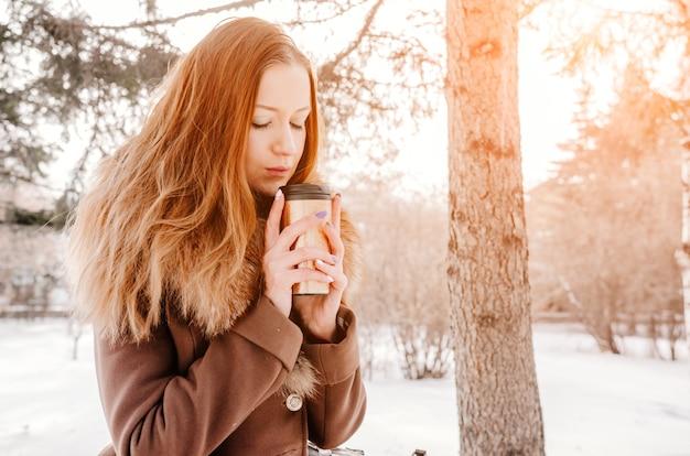 Femme avec une tasse de thé ou de café dans le parc d'hiver