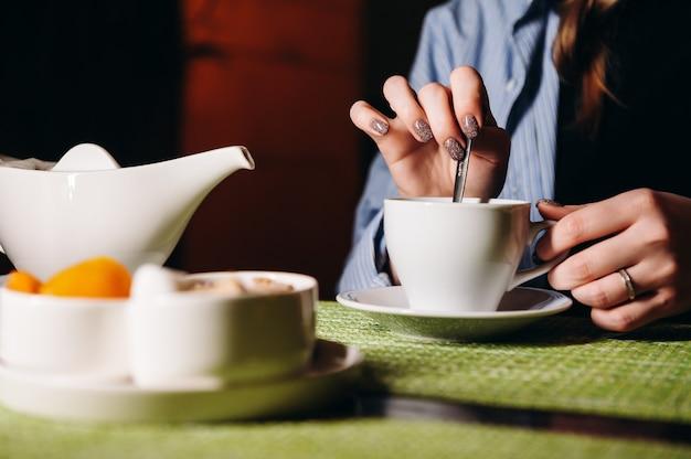 Une femme avec une tasse de thé chaud dans les mains est assise dans le restaurant la fille boit du thé aromatique profitez du moment pour faire une pause