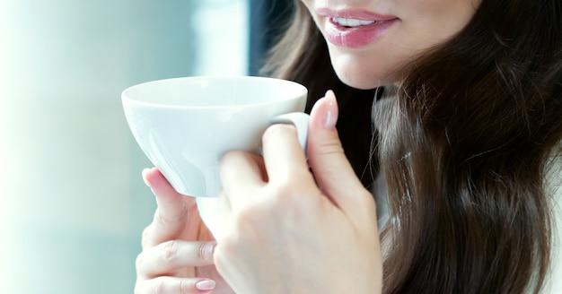 Femme et tasse de thé se bouchent