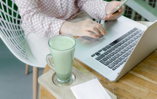 Femme tasse vert matcha latte café thé en verre lieu de travail café terassa home freelancer