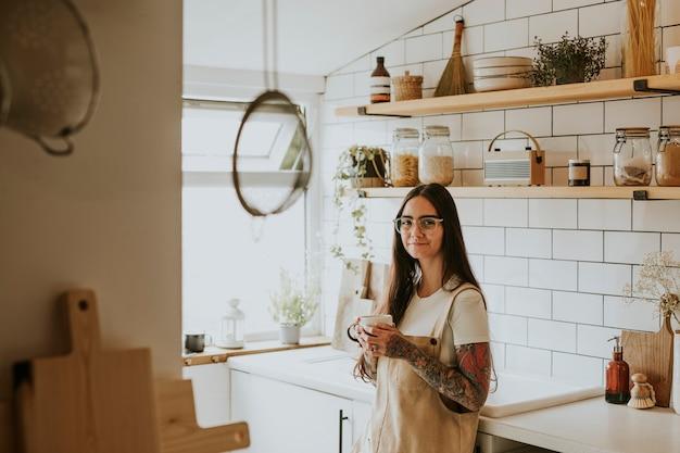 Femme tatouée appréciant le thé dans sa cuisine confortable