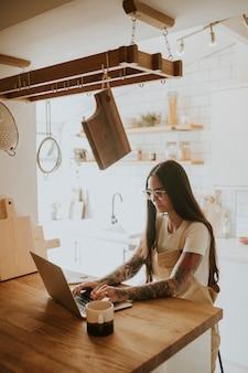 Une femme tatouée dans la trentaine travaille à domicile