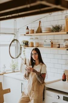 Femme tatouée se détendre dans sa cuisine avec une tasse de thé