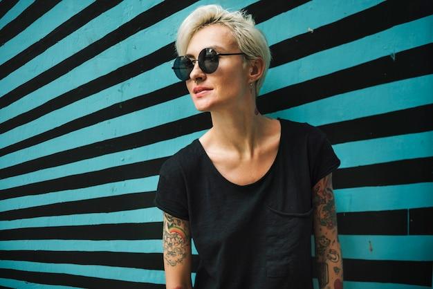 Femme tatouée en t-shirt noir avec fond rayé