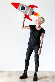 Femme tatouée tenant l'icône de rocketship