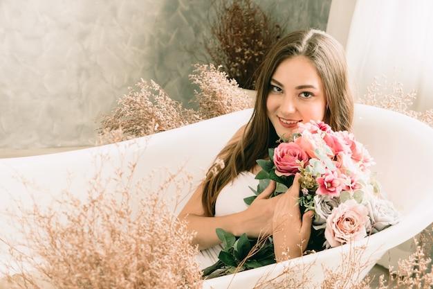 Femme teen mignonne souriante dans la baignoire avec la photographie de modèle d'art vintage fleur
