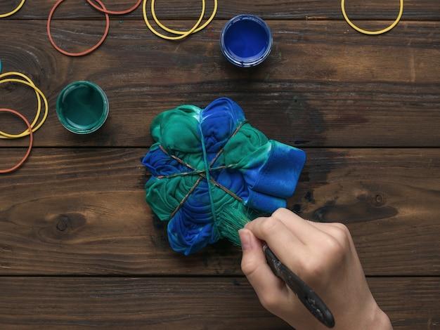 Une femme teint un tissu à la maison.