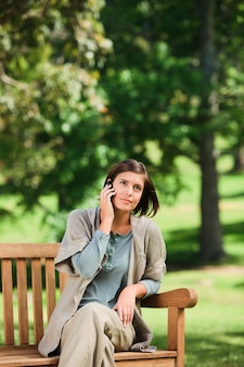 Femme téléphonant sur le banc