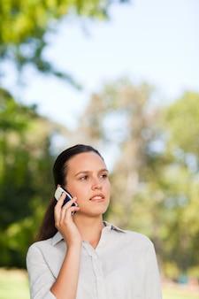 Femme téléphonant dans le parc