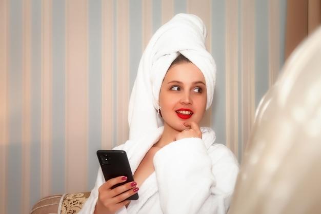 Femme avec téléphone sur canapé de chambre d'hôtel après la douche. jolie femelle d'apparence slave en robe de chambre et serviette sur la tête. heureuse dame. leçon avec smartphone. jolie fille après lavé