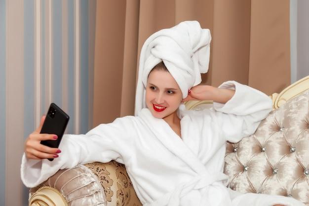 Femme avec téléphone sur canapé de chambre d'hôtel après douche
