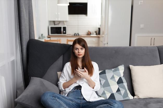 Femme avec un téléphone dans ses mains, assis sur une technologie de week-end de loisirs canapé confortable.