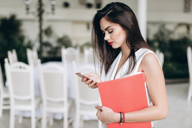 Femme Avec Téléphone Et Dossier Photo Premium