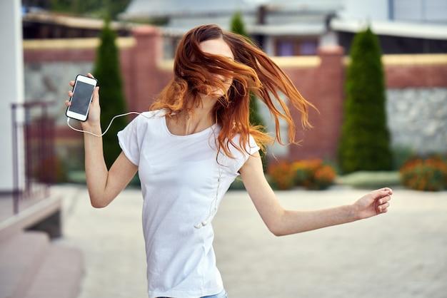 Femme, téléphone, écouteurs, courses