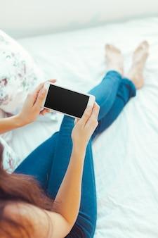 Femme avec un téléphone mobile moderne dans les mains