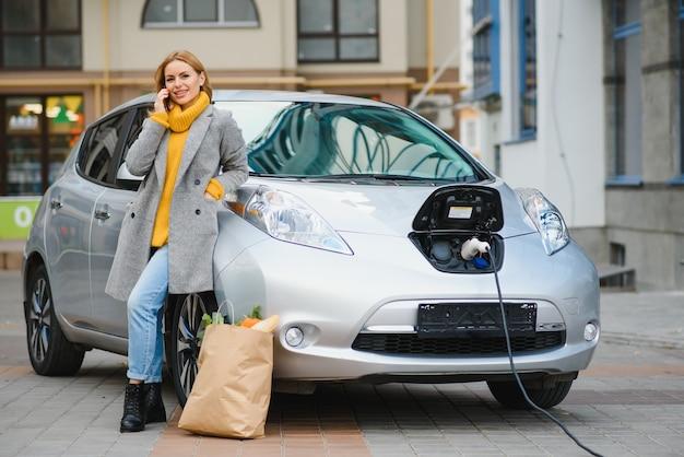 Femme avec téléphone près d'une voiture électrique de location